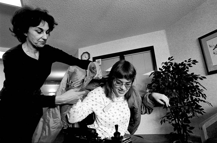 Colleague Sandy McCormick helps Theresa get ready for going out. The two of them work at Montana Independent Living, an agency for assisting people with disabilities.